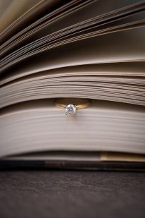 Solitaire diamond engagement ring, close up shot idea in the pages of a book.  by Awakened Light Photography, Michigan wedding photographer