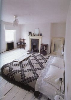Quilt / black fireplace / mirror & framed pictures.