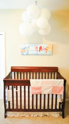 Paper balloons over crib in this fun baby girl's room