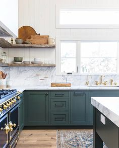 Amber Interiors is another perpetual favorite, and we love this combination of wood and marble with the dark green cabinets! Image via Amber Interiors. Green Kitchen Cabinets, Kitchen Cabinet Colors, Painting Kitchen Cabinets, New Kitchen, Kitchen Dining, Kitchen Decor, Kitchen Ideas, Dark Green Kitchen, Stylish Kitchen