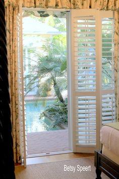 love this fiberglass shutters over sliding glass doors where french doors