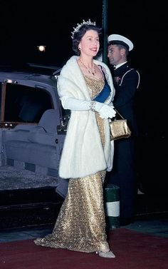 Queen Elizabeth II wearing a dramatic golden gown and white fur stole in London.