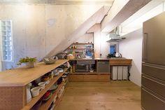 階段下の斜めの躯体が印象的な、L字型の大型の造作キッチン。シンクが一体型のステンレス天板を特注。