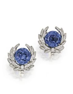 PAIR OF PLATINUM, SAPPHIRE AND DIAMOND EARCLIPS, VERDURA. Set with two round sapphires weighing approximately 11.80 and 10.05 carats, framed by wreaths set with numerous round diamonds weighing approximately 3.60 carats, signed Verdura, with workshop marks; fitted with pendant hooks. With signed box.
