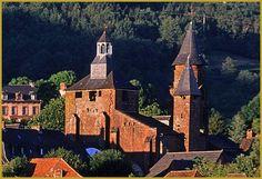 Photo dans une belle lumière du soleil couchant du donjon fortifié et des tours de l'église Saint-Pierre qui surplombe le village de Collonges-la-Rouge; un édifice roman classé aux Monuments Historiques depuis 1905. Photos de Collonges-la-Rouge.