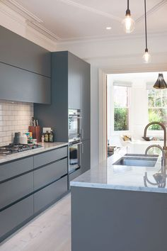 Stylish modern kitchen in shades of bluish-gray and white is an absolute…