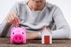 woman inserting money in a piggy bank and model home