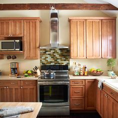 Mind the Hood A sleek, wall-mount vent hood over the cook top trims the visual fat from a wall of cabinets, giving the room a greater feeling of openness. Minimalist vent hoods like this one require 30 inches between cabinets, about the same as an undercabinet hood, but give a cleaner, lighter look -- a plus in a small kitchen.