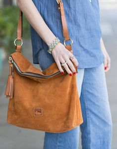 brown suede crossbody bag with tassel from dooney and bourke