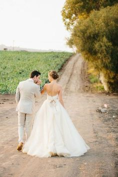 This is another picture of photo representation that the man and women have just been married and they look as if they are about to walk down a road together because it is a mark of starting a journey together because they are married.