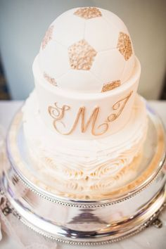 Ivory and gold wedding cake, incorporating a soccer ball. Images by Danylo Bobyk Photography : :www.danylobobykweddings.com