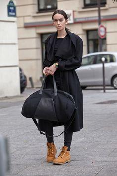 Acheter la tenue sur Lookastic: https://lookastic.fr/mode-femme/tenues/manteau-t-shirt-a-manche-longue-pantalon-slim-bottes-grand-sac-montre/7254 — T-shirt à manche longue noir — Manteau noir — Montre dorée — Bottes en daim brunes claires — Pantalon slim en cuir noir — Grand sac en toile noir