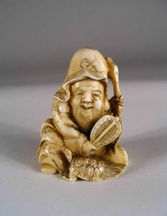 ivory netsuke of Fukurokuju holding a fan in one hand and his staff in the other. Immediately recognizable by his tall, domed forehead, Fukurokuju is a Japanese deity of happiness, prosperity, longevity, and wisdom. Here he is depicted seated with a hairy tailed turtle (minogame) at his feet, also a symbol of longevity which is purported to live 10,000 years.