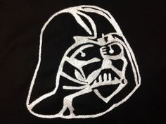 Detail from Darth Vader Cloak. Approximately 25cm sized embroidery of Darth Vader's mask. Used long and short stitch in DMC stranded cotton thread blanc, gone over in long stitch with Kreinick metallics blending filament 032 and stem stitch outline in DMC precious metal effects E317. Stitched for 5 year old nephews xmas present of a 'Darth Vader Cloak'. Stitched December 2013.