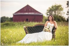 Bride on couch in a field with a red barn #wedding #bridal…