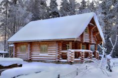 Great looking log house with twin storeys and front veranda covered in fresh snow