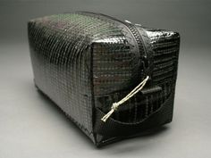 A carbon fiber sailcloth shave kit or toiletry gear bag with a zippered end pocket for little items.  $65    http://store.carbonfibergear.com/raggededge-sailcloth-toiletry-bag-carbon-fiber-black
