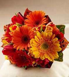 The FTD® Sunglow™ Bouquet is a blooming wish for happiness and sunlit cheer throughout your lifetime together. Red, orange and bi-colored orange tulips are brought together with red, orange and gold g