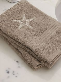 Starfish embroidered bath towel for your beach house. Discover more styles at jacarandaliving.com