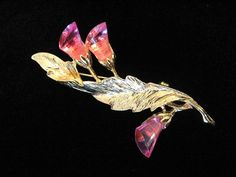 Vintage Park Lane floral leaf brooch with gold tone finish. This is a simply beautiful leaf pin accented with three translucent pink Lucite flowers. The pin is signed and in excellent vintage condition. (Owned by a former Park Lane distributor and might not have been worn or used as a demo only.) Approx. size - 3 L.  *Jewels by Park Lane - Founded by Arthur and Shirley LeVin, 1955 – Present, Chicago, IL. A family business, now run by Levin's children, Scott, Mark, and Arthur Levin. Sold at…