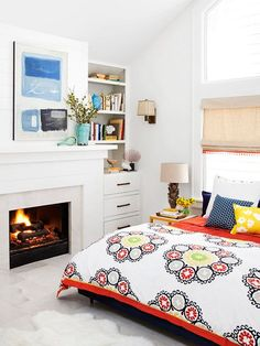 With a backdrop of stark white, anything goes in terms of colorways. A navy, yellow, and red bedspread brings a cheerful tone to the room. Accessories spread color throughout the bedroom while keeping in step with the bedspread. The painting above the mantel pulls blue and white tones from the spread, while orange sheets enhance the red and yellow.