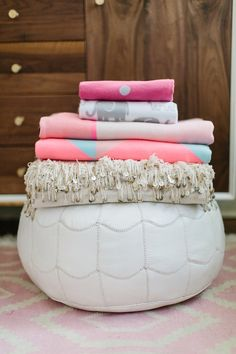 Show off your blanket collection by displaying them on a pretty pouf.