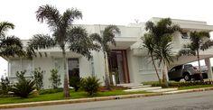 Fachada Sobrado, porta de entrada pivotante em madeira, caixilhos em aluminio, guarda corpo em aluminio branco. garagem coberta, varanda. Gramado, paisagismo, coqueiros. Cores neutras. Arquiteta Danyela Corrêa