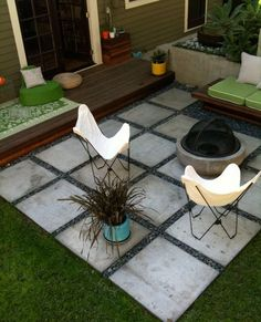 small backyard--love combo of stones around pavers and dark wood decking