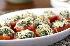 """Fresh spinach and """"cocktail"""" tomatoes pair together perfectly in these Spinach Stuffed Tomatoes for a colorful, healthy bite-size appetizer."""