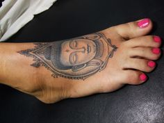 Buddha tattoo on the dorsal part of a woman's foot.