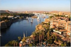 Aswan, Egypt: the hottest place I've ever been to.  At dusk, locals gather in the street and delicious cooking smells drift through the town.  Friendly locals, beautiful scenery.