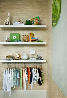 wall. would never have thought to hang clothes on the bottom of a shelf.  Good idea for a room without a closet.