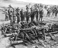 American Generals George Patton, Omar Bradley, and Dwight David Eisenhower in the Ohrdruf concentration camp stand at a pyre where SS soldiers had burned bodies of dead prisoners.