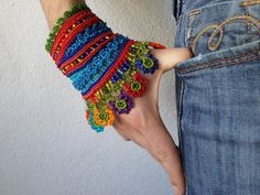 colorful beaded cuff bracelet with turquoise blue and bright red crocheted base and beaded crochet flowers in rainbow colors by irregularexpressions
