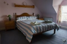 Master bedroom at Sandcastle Cottage - comfy bed and a view towards Roome Bay