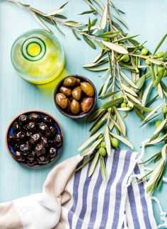 Two bowls with pickled green and black olives olive tree sprigs fresh homemade oil over blue by 2enroute  IFTTT 500px