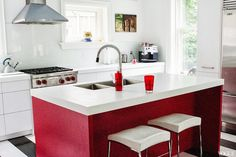 Kitchen in Vogue.com contributorSophie Young's childhood home with black and white striped floor, red island and stainless appliances