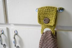 Tea towel holder with an ouchless ponytail elastic inside. - I would make it quilted rather than crochet though. and maybe a snap rather than a button?