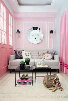The pink walls set off the soft, gray sofa, making for a cozy living area where the owner can relax after a tiring day at work.