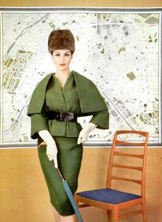 Jean Newington in green wool suit with belted jacket that has short capelet, by Nina Ricci. Photo by Philippe Pottier, 1959