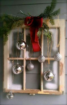 Ornaments with raffia string on old window with greenery and red ribbon