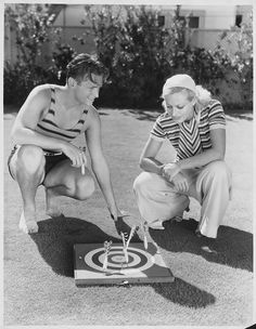 Actress Joan Crawford and husband Douglas Fairbanks, Jr. play a game of lawn darts outside their home.