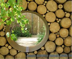 portal..wall od stacked logs with round portal opening to patio or garden
