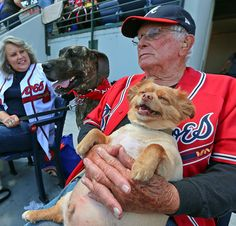 """HAPPIEST DOG IN THE WORLD! George Lavery, 84, and his dog """"Chipper,"""" named after Chipper Jones, soak up the sun during """"Bark in the Park"""" at Turner Field while the Braves play the Mets on Sunday, May 5, 2013, in Atlanta. At left is Cindy Buchanan and her Great Dane Brie.  (Curtis Compton/Atlanta Journal-Constitution/AP)"""