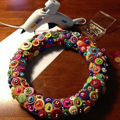"""Awesome button wreath!  Two Chicks Designs  1. I started with these buttons. I have lots and lots of buttons left. I used a 12"""" Styrofoam wreath and straight pins with white heads. I used about 300 straight pins, so I am estimating I also used about 300 buttons as well.  2. I stacked the buttons in color combos I liked and pinned them directly to the wreath. I stacked two or three buttons each time and used two pins for each set.  3. Saturday I used a hot glue gun to add some of the buttons"""