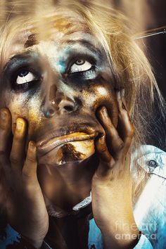 Close picture of a scary female zombie pulling funny face while looking up the light shining from above by Ryan Jorgensen
