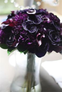 Dark purple bouquet of deep purple callas, deep purple carnations, and freeze dried purple roses