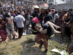 Rescue workers carry a childs body from the scene on Wednesday. (Photo by A. M. Ahad/Associated Press)
