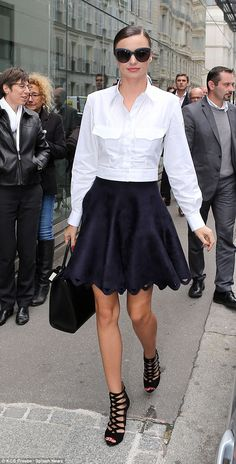 Demure dresser: Miranda Kerr looked chic in a white shirt and flared navy skirt as she hit the designer boutiques during Paris Fashion Week on Wednesday