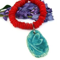 "The ""Libellula"" one of a kind handmade necklace, was created with a unique artisan made ceramic dragonfly pendant with a teal turquoise glaze, red coral discs and sterling silver."
